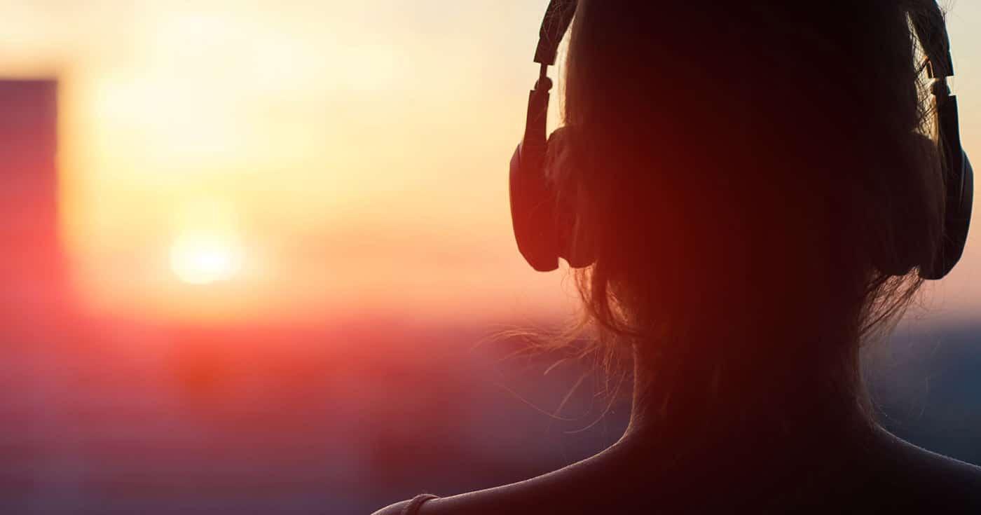 Femme écoutant de la musique face au soleil
