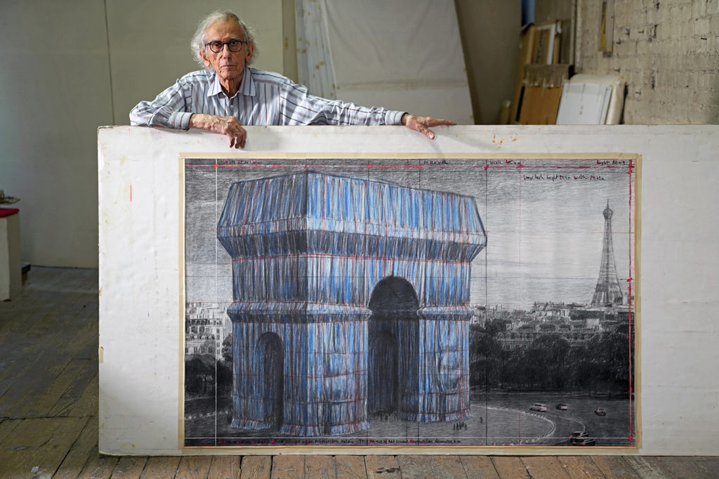 """Christo in his studio with a preparatory drawing for """"L'Arc de Triomphe, Wrapped"""" - New York, September 20, 2019, Photo by Wolfgang Volz 2019 © Christo and Jeanne-Claude Foundation"""
