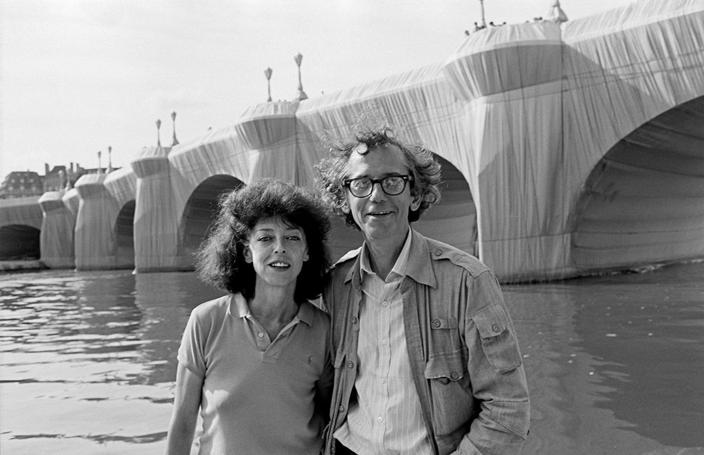 """Christo and Jeanne-Claude in front of """"The Pont Neuf Wrapped,"""" Paris, 1985, Photo by Wolfgang Volz 2019 © Christo and Jeanne-Claude Foundation"""